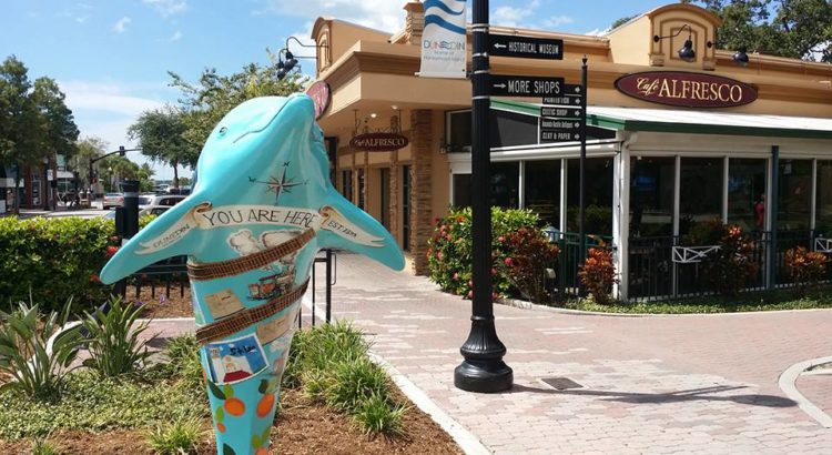 Exterior shot of Cafe Alfresco in Dunedin, Florida with a Dunedin dolphin statue