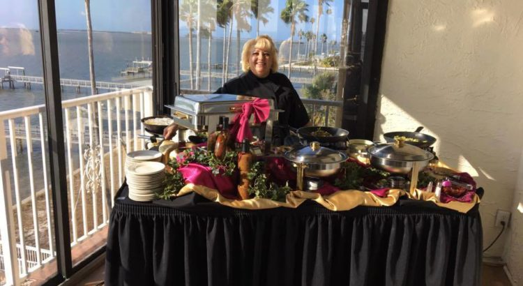 chef behind a table of catered food overlooking the water at Beso Del Sol Resort
