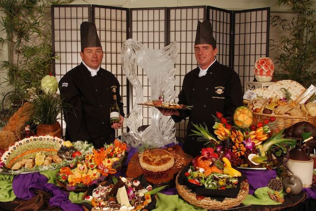 two chefs in front of a Delectables ice sculpture